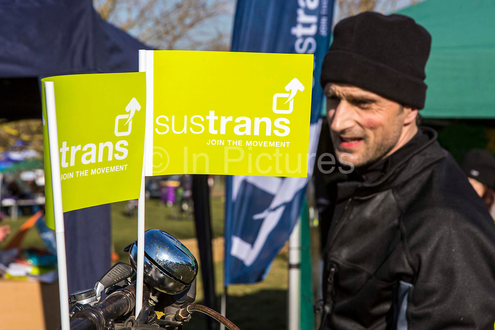 A male cyclist proudly displaying Sustrans flags on his bicycle handlebars at the opening of the Bath Two Tunnels Greenway on 6th April 2013 in Somerset, United Kingdom.  He is part of a large group of cyclists and pedestrians celebrating the restored railway tunnels which link 13-miles through the beautiful country-side.  The restoration of the tunnels was organised by Sustrans, working in partnership with Bath and North East Somerset Council.   Sustrans is a charity that works with communities, policy-makers and partner organisations so that people can choose healthier, cleaner and cheaper journeys and enjoy better, safer spaces to live in. The event was attended by hundreds of cyclists and pedestrians of all ages and abilities. Bath, Somerset, United Kingdom.