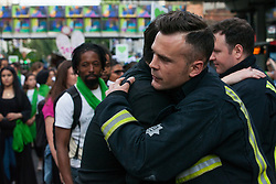 London, UK. 14th June, 2018. Members of the Grenfell community thank firefighters from the London Fire Brigade forming a guard of honour for the Grenfell Silent March through West Kensington on the first anniversary of the Grenfell Tower fire. 72 people died in the Grenfell Tower fire and over 70 were injured.