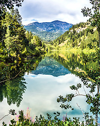 Little Elk Creek Canyon and Mount Baird of the Snake River Range reflecting in the still waters of Palisades Reservoir in Swan Valley Idaho