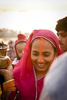 A bride walks amont the pilgrims on the ghats during the festival of Kartik Poornima in Varanasi, Uttar Pradesh, India