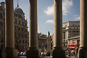 Lunchtime spring crowds enjoy warm weather beneath the pillars at Cornhill Exchange in the City of London.