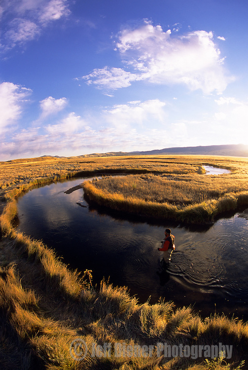 A young man fishes at sunrise on Flat Creek in Jackson Hole, Wyoming.