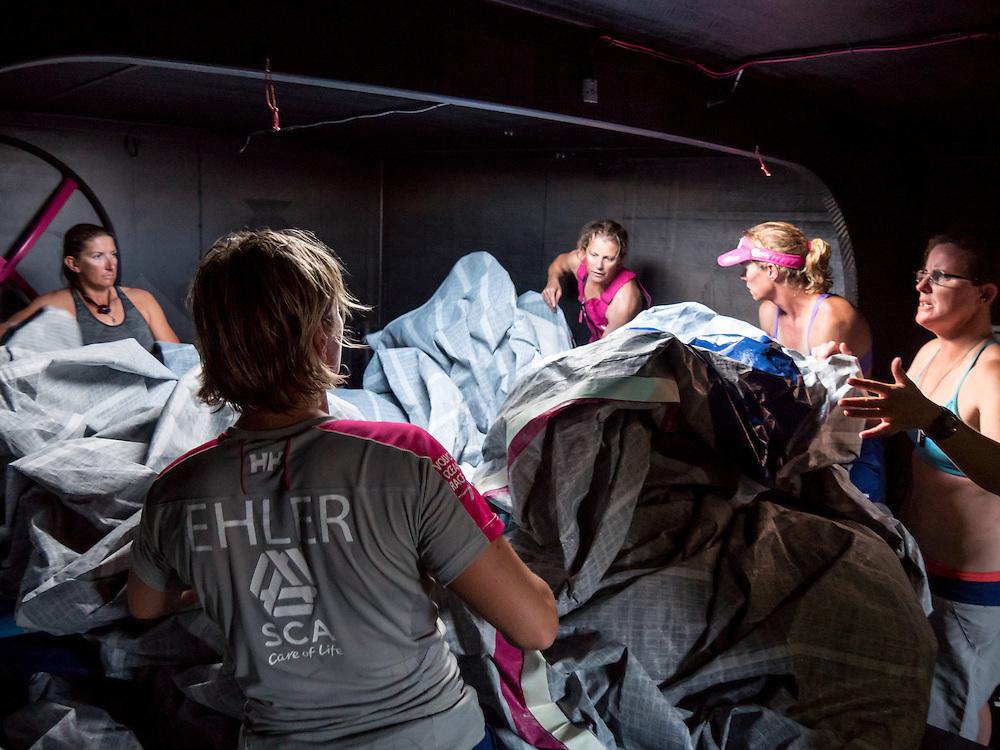 January 17, 2015. Day 14 of Leg 3 to Sanya, onboard Team SCA. Team Effort. Dee Caffari, Abby Ehler, Sam Davies, Carolijn Brouwer, and Stacey Jackson untwist the Mast Head Zero after it's major sail repair.