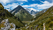 Rees-Dart Track follows Snowy Creek from Rees Saddle down into Dart Valley in Mount Aspiring National Park, Otago region, South Island of New Zealand. Glacier-clad Mt Edward rises on right; on left is Fernier Glacier on 2480m Mt Lydia. This image was stitched from multiple overlapping photos.