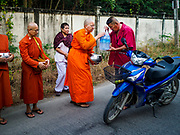 13 JANUARY 2019 - NAKHON PATHOM, THAILAND: DHAMMAVANNA, a female monk at Wat Songdhammakalyani, accepts bottled water from a man during the monks' alms rounds. The Sangha Supreme Council, Thailand's governing body of Buddhist monks, bans the ordination of female monks, but hundreds of Thai women have gone abroad, mostly to Sri Lanka and India, to be ordained. There are about 270 women monks in Thailand and about 250,000 male monks. There are 7 monks and 6 novices at Wat Songdhammakalyani in Nakhon Pathom. It was the first temple in Thailand to have female monks. The temple opened 60 years ago and has always been a temple of women monks. Women can be ordained as novices in Thailand, but to be ordained as a full monk would require the participation of 10 female monks and 10 male monks, and male monks in Thailand are barred from participating in women's ordination ceremonies.    PHOTO BY JACK KURTZ