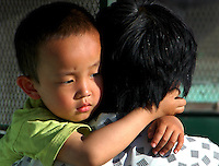 China, Taiyuan, 2008. An apprehensive boy seeks the comfort of his mother's arms after kindergarten. Parents with bikes regularly converge on school gates to pick up their children..