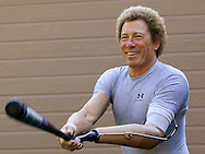 """Bob Radocy of TRS Inc. smiles as he swings a baseball bat with his """"Grand Slam Tds."""" prosthetic hand at his home in Boulder, Colorado August 20, 2009. Radocy designs and builds prosthetic attachments that allow amputee athletes to participate in multiple sports.  REUTERS/Rick Wilking (UNITED STATES)"""