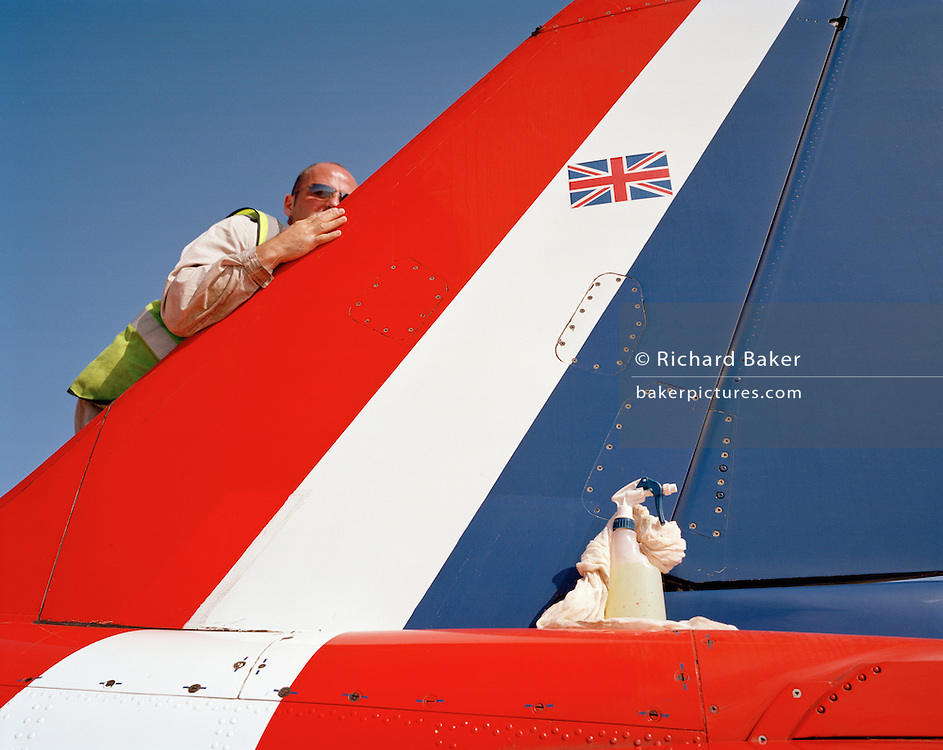 Specialist Corporal Mal Faulder is an armourer engineer (qualified to handle ejection seats and weaponry on military jets) but here in the elite 'Red Arrows', Britain's prestigious Royal Air Force aerobatic team he is seen polishing the aircraft's flying surfaces using wool and cleaning fluid on the morning of the team's PDA Day. PDA (or 'Public Display Authority'), is a special test flight when their every move and mistake is assessed and graded. Corporal Faulder is to buff up the airplane for an extra special shine on such an important day and we see the UK's Union Jack flag on the side of the diagonal stripes of the tail fin. The Red Arrows ground crew take enormous pride in their role as supporting the aviators whose air displays are known around the world. Blues like Mal outnumber the pilots 8:1. Without them, the Red Arrows couldn't fly.