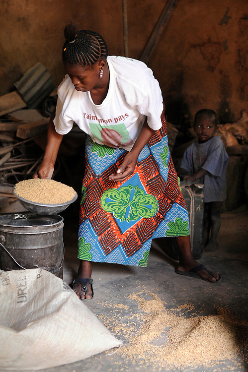 African farm labourers use machine as they separate grains of rice from the husk at a grain market in Natitingou, Benin on February 25, 2008.