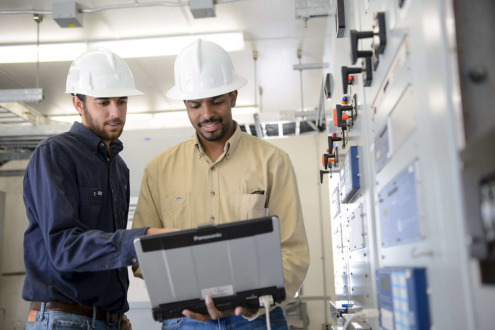 Network engineers working at a power plant substation.