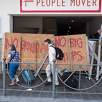 VENICE, ITALY - JUNE 06: Two tourists walk in front of the blocked entry to the People Mover railway staion block the People Mover railway station on June 6, 2014 in Venice, Italy. Todays protest was to highlight one again the problem of the big cruise ships in Venice and the major works as the MOSE, TAV or Expo 2015.  (Photo by Marco Secchi/Getty Images)