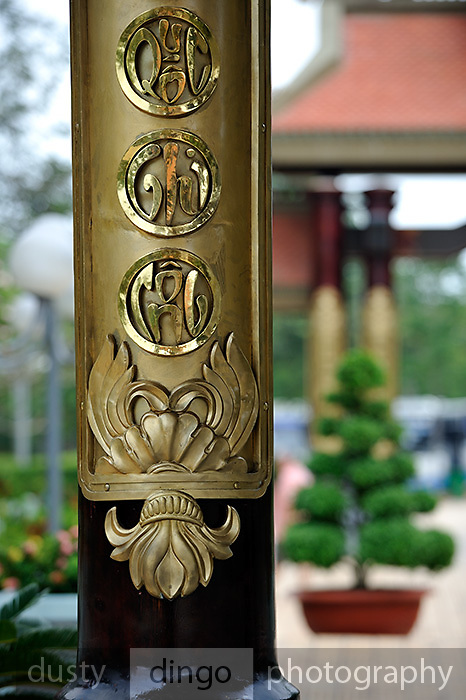 Detail of one of the wooden pillars of the three-door temple gate of the Ben Duoc Monument to War Martyrs, bearing the words of the Vietnamese poet Bao Dinh Giang..The memorial complex was built to honour the contributions of the soldiers and people who sacrified their lives in the Saigon - Gia Dinh region during the anti-American and the anti-French struggles. The names of 44,520 revolutionary martyrs are carved with gilded letters into a granite stone tablet in the main temple, including Vietnamese mothers, heroes, and revolutionary martyrs, and 9,322 revolutionary martyrs from other provinces and cities. Cu Chi, Vietnam