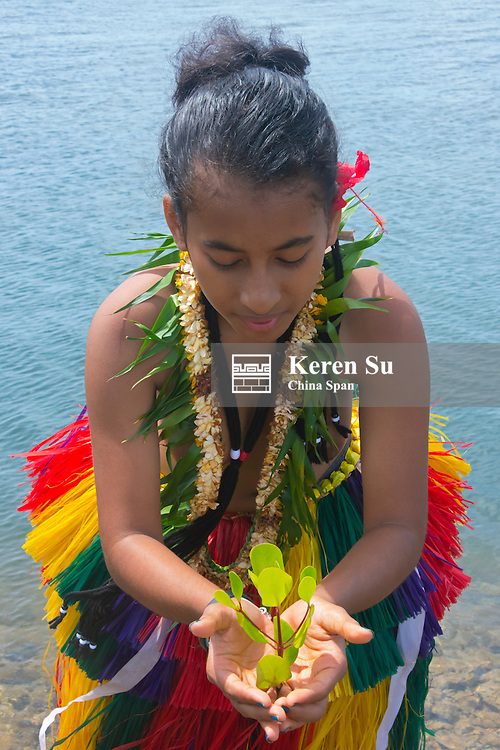 Yapese girl in grass skirt holding a plant, Yap Island, Federated States of Micronesia