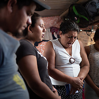 A family who lost their house in hurricane Eta pray inside a makeshift shelter on the side of the road in Chamelecón, San Pedro Sula. One of the members of the family is part of a CASM-supported programme for deported migrants.