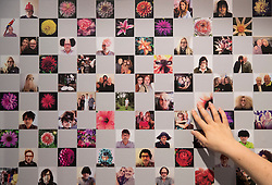 © Licensed to London News Pictures. 01/11/2016. London, UK. A visitor to the 'Hair by Sam McKnight' exhibition at Somerset House reaches out to touch an Instagram wall showing images collated from the hair stylist's feed. The show, which runs from 2nd November, 2016 to 12th March, 2017, celebrates the career of fashion's favourite hair stylist. Photo credit: Peter Macdiarmid/LNP