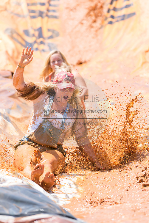 A group of children slip down a mud slide during the 2015 National Red Neck Championships May 2, 2015 in Augusta, Georgia. Hundreds of people joined in a day of country sport and activities.