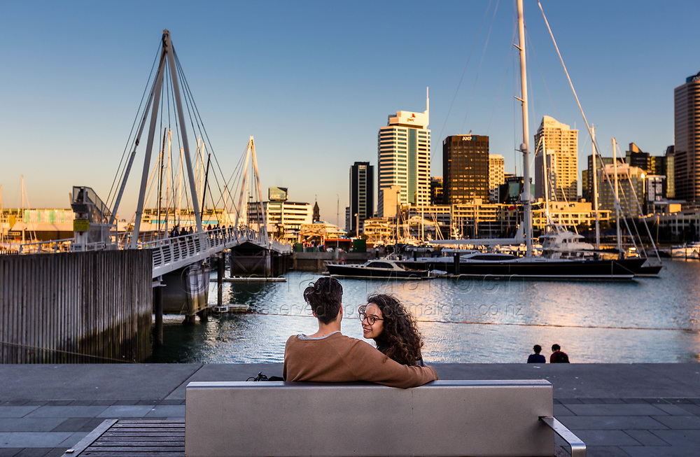 American Way Neighborhood Watch: Auckland Waterfront, photographed November 2017 – New Zealand. <br /> Josh Huirua and Polyana Rodrigues Silva enjoy relaxing at Karanga Plaza as the sun sets on the city, with the Wynyard Crossing Bridge in the foreground, and the Viaduct behind.