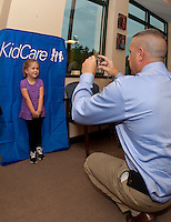 Maya Heller flashes a big smile for Gilford Police Detective Sgt. Kris Kelley as he takes her picture to put in her Child ID booklet at the office of Children's Dentistry of the Lakes Region Thursday afternoon.(Karen Bobotas/for the Laconia Daily Sun)