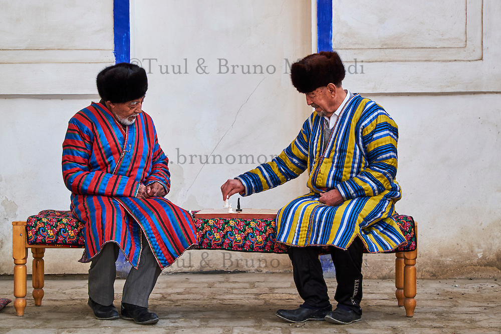 Ouzbekistan, Boukhara, hommes Ouzbek en chapane, aux habits traditionnels, jouant aux echecs // Uzbekistan, Bukhara, Unesco world heritage, Uzbek men playing chess in traditional clothes chapan