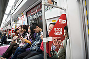 A woman looks at her phone while riding a subway train in Shenzhen, China, on Thursday, Dec. 17, 2015.