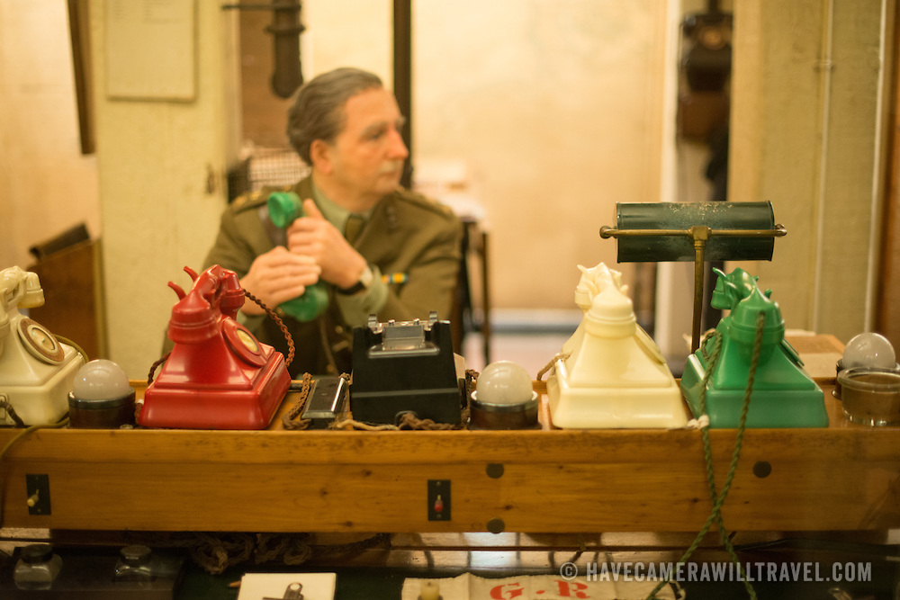 A manequin of an officer on the telephone in the Map Room at the Churchill War Rooms in London. The museum, one of five branches of the Imerial War Museums, preserves the World War II underground command bunker used by British Prime Minister Winston Churchill. Its cramped quarters were constructed from a converting a storage basement in the Treasury Building in Whitehall, London. Being underground, and under an unusually sturdy building, the Cabinet War Rooms were afforded some protection from the bombs falling above during the Blitz.