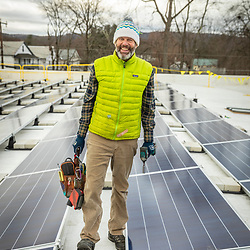 PV Squared employee Jeff Molongoski installing solar panels on the roof of a commercial building in Greenfield, Massachusetts.