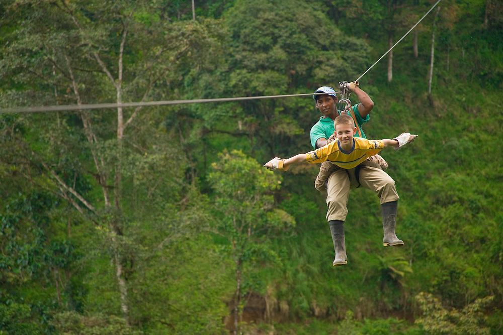 South America, Ecuador, Mindo.  Boy tourist (age 9) and guide  riding zip-line through cloudforest canopy.  MR