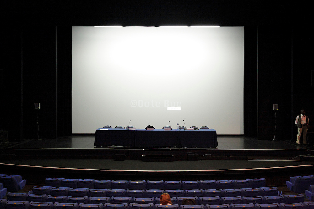 large blank projection screen and empty stage in a conference hall