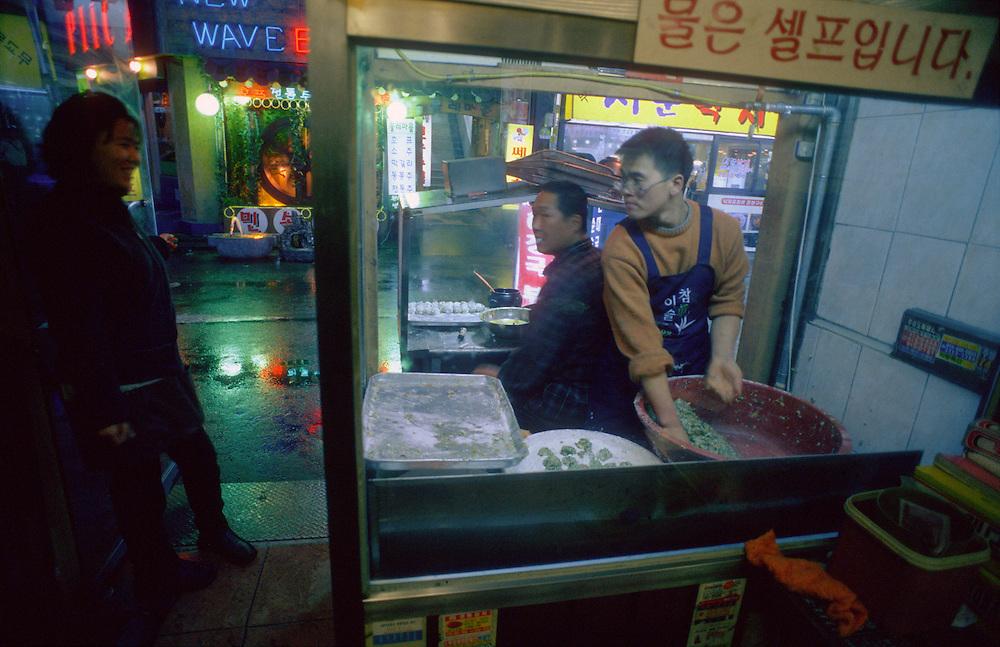 Two chefs talk with a customer as they prepare street food, Gwanghwamun area, Seoul, South Korea.