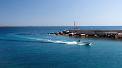 Piccola barca a motore entra a velocità sostenuta nel porto Pescherecci di Gallipoli (LE)