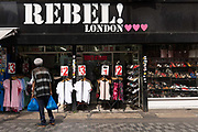 A man walks towards a clothing fashion shop on Electric Avenue in Brixton called Rebel London on the 24th July 2019 in South London in the United Kingdom.