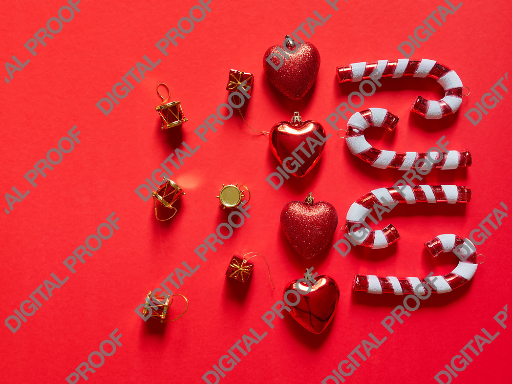 Christmas candy cane drums hearts and gifts at studio above view over a red background isolated flatlay