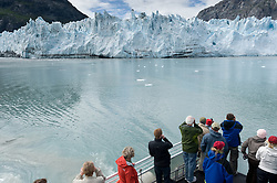 Tourists on the daily tour boat, Baranof Wind, photograph the face of Margerie Glacier, one of the seven tidewater glaciers in Glacier Bay National Park and Reserve in southeast Alaska. The Margerie Glacier is located on the Tarr Inlet next to another tidewater glacier, Grand Pacific Glacier. Margerie Glacier's one mile wide face has a total height of 350 feet, out of which 250 feet is above the water level and 100 feet is beneath the water surface. For comparison purposes the Statue of Liberty is 307 feet tall. The length of the glacier (2011) is approximately 21 miles.
