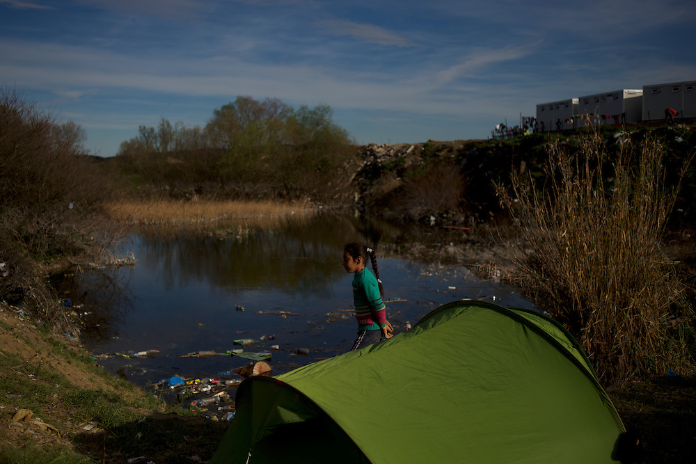 A Syrian child walks by a tent set up beside a waste pond near the border between Greece and Macedonia in Idomeni, Greece. Around 13,000 migrants and refugees, mostly from the Middle East and African nations, are believe to be stranded here awaiting a chance to proceed their journey towards Germany and other northern European countries.