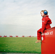 A young boy wearing ear-defenders and dressed in a child's miniature red flying suit is perched on a metal crate of flight spares belonging to the elite 'Red Arrows', Britain's prestigious Royal Air Force aerobatic team. Joshua Lewis is the son of one of the team's electricians Corporal Dave Lewis, and they are both at RAF Scampton in Lincolshire to wave goodbye to the departing Hawk jet aircraft who are leaving for their winter training ground at Akrotiri, Cyprus. Other team-member families have come along to see these famous red aircaft. Most of the team leave the UK for a six-week stint, refining their evolving air display routines and manoeuvres in the clear Mediteranean skies. Pilots and ground support crew will be away from loved-ones and their absence is one of the toughest aspects of RAF frontline personnel - and aerobatic squadrons.
