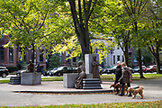 Local people walking their dogs by the Boston Women's Memorial in Commonwealth Avenue Mall in Boston, USA