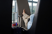 A resting passenger sleeps on a circular couch near airport gates during his layover transit period at Heathrow airport's T5