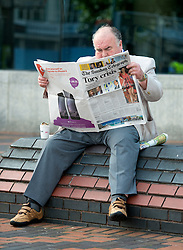 © Licensed to London News Pictures. 28/09/2014. Birmingham, UK. A delegate reads a copy of the Sunday Telegraph outside the conference centre. The Conservative Party Conference in Birmingham 28th September 2014. Photo credit : Stephen Simpson/LNP