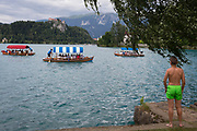 With Bled Castle at the top of cliffs, a tourist boat takes tourists on a tour of Lake Bled watched by a boy, on 18th June 2018, in Bled, Slovenia.