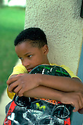 Boy age 10  musing with skateboard on a porch.  St Paul  Minnesota USA