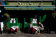 People sit outside in the sunshine having lunch outside the Mediterranean restaurant on Berwick Street in Soho, London, UK. This scene with these colours and the light could almost be a European mainland scene.
