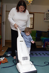Mother vacuuming with her toddler son helping,