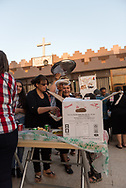 A parishioner encourages a photographer to eat during a church meal in the courtyard of Saint John the Baptist Church (Ancient Church of the East) in Kirkuk, Iraq. (May 21, 2017)