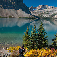 A photographer frames Crowfoot Mountain, Portal Peak, Mount Thompson and Bow Lake in Banff National Park, Alberta, Canada.