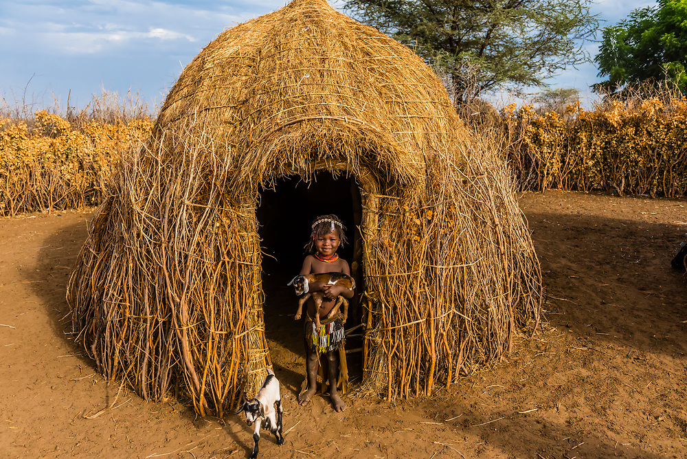 Young Nyangatom tribe girl holding a goat in front of her hut, Omo Valley, Ethiopia.