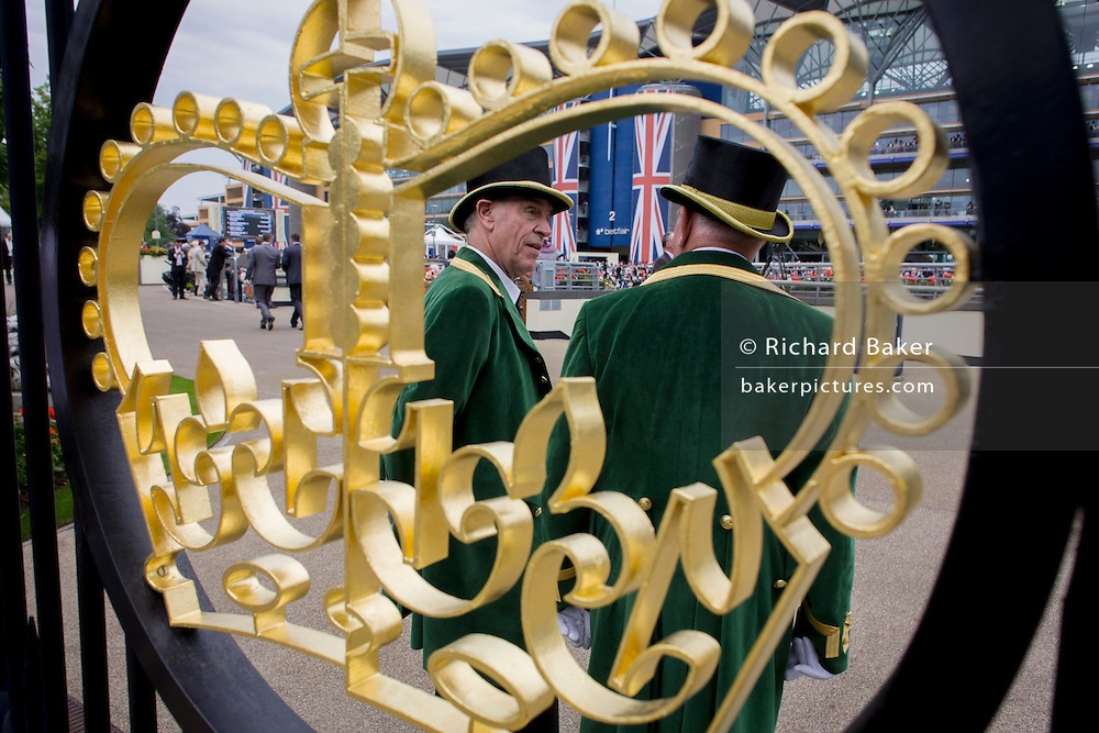 Official Gatekeepers seen through the crown design at the entrance during the annual Royal Ascot horseracing festival in Berkshire, England. Royal Ascot is one of Europe's most famous race meetings, and dates back to 1711. Queen Elizabeth and various members of the British Royal Family attend. Held every June, it's one of the main dates on the English sporting calendar and summer social season. Over 300,000 people make the annual visit to Berkshire during Royal Ascot week, making this Europe's best-attended race meeting with over £3m prize money to be won.