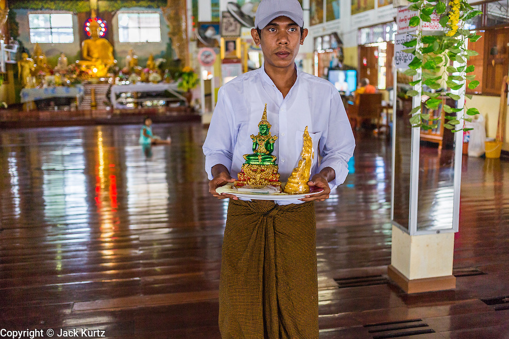 24 MAY 2013 - MAE SOT, THAILAND:    A Burmese man puts away statues of the Buddha in Wat Pha Mai after Visakha Puja Day services. Visakha Puja (Vesak) marks three important events in the Buddha's life: his birth, his attainment of enlightenment and his death. It is celebrated on the full moon of the sixth lunar month, usually in May on the Gregorian calendar. This year it is on May 24 in Thailand and Myanmar. It is celebrated throughout the Buddhist world and is considered one of the holiest Buddhist holidays. Burmese Buddhist in Mae Sot celebrated with a procession through Mae Sot that ended with a service followed by a communal meal at Wat Pha Mai, the most important Burmese Buddhist temple in Mae Sot.   PHOTO BY JACK KURTZ