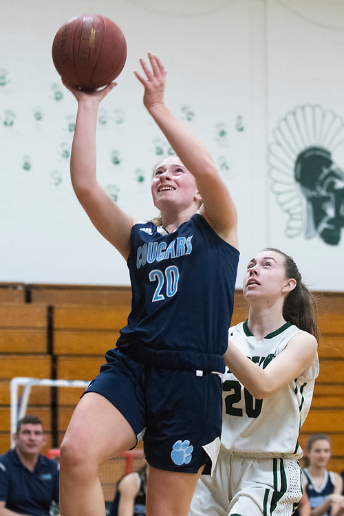 MMU's Meadow Worthley (20) leaps past Winooski's Michaela Parris (20) for a layup during the girls basketball game between the Mount Mansfield Cougars and the Winooski Spartans at Winooski High School on Friday night February 14, 2020 in Winooski, Vermont.(BRIAN JENKINS/for the FREE PRESS)
