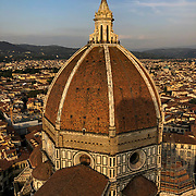 The view from the top of Giotto's Bell Tower of the Duomo cupola, or dome with Florence, Italy beyond.