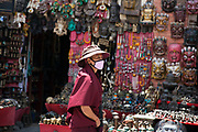A Buddhist monk at the Swayambhunath temple complex, also called the Monkey Temple. Souvenirs to buy are on display.